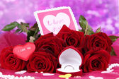 Beautiful bouquet of roses with valentine on pink fabric on purple background close-up — Stock Photo