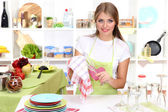 A young girl dries dishes in kitchen — Stock Photo