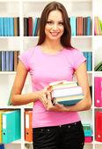 Giovane studentessa attraente con i suoi libri di scuola in biblioteca — Foto Stock