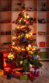 Decorated Christmas tree on home interior background at night — Stockfoto