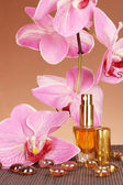 Women's perfume in beautiful bottle with orchids on brown background — Stock Photo