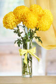 Bright yellow chrysanthemums in glass vase, on wooden table — Stock Photo