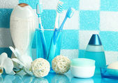 Bath accessories on shelf in bathroom on blue tile wall background — Stock Photo
