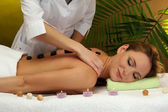 Beautiful young woman in spa salon getting massage with spa stones, on green background — Stock Photo