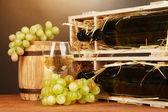 Dřevěné pouzdro s láhev vína, barel, skleničku a hroznů na dřevěný stůl na hnědé pozadí — Stock fotografie