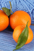 Sweet tangerines with leaves, on blue yarn background — Stock Photo