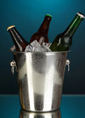 Beer bottles in ice bucket on darck blue background — Stock Photo