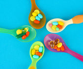 Plastic spoons with color pills on blue background — Stock Photo