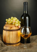 Composition of wine and grapes on wooden barrel on sackcloth — Stock Photo