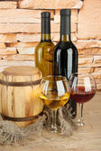 Composition of wine and wooden barrel on table on brick wall background — Stock Photo