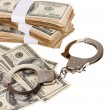Handcuffs and packs of dollars on white background close-up - Stock Photo