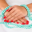 Female hands holding beads on color background — Foto Stock