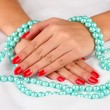 Female hands holding beads on color background - Stockfoto
