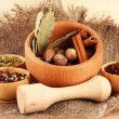 Nutmeg and other spices on sackcloth background - Stock Photo