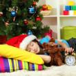 Little girl sleeping near christmas tree — Stock Photo #18293599