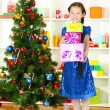 Foto Stock: Little girl holding gift box near christmas tree