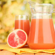 Full glass and jug of grapefruit juice and grapefruits on wooden table outdoor — Stock Photo #18294115