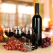 Red wine in glass and bottle on room background - Stock Photo