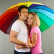 Loving couple with umbrella on grey background — Stock Photo
