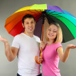 Loving couple with umbrella on grey background — Stock Photo #18294431