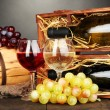Wooden case with wine bottles, barrel, wineglass and grape on wooden table on grey background — Stock Photo #18294469