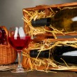 Wooden case with wine bottles, wineglass and grape on wooden table on grey background — Stock Photo