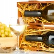 Wooden case with wine bottle, wineglass and grape isolated on white — Stock Photo