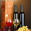 Wooden case with wine bottles on wooden table on brown background — Stock Photo