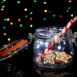 Tasty cookies in glass bottle on blur lights background — Stock Photo #18294709