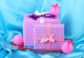 Beautiful purple in peas gifts with pink Christmas balls, snowflakes and beads on blue background — Stock Photo