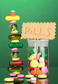 Capsules and pills hill and in receptacle on green background — Zdjęcie stockowe