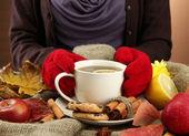 Ruce držící šálek horké nápoje a podzimní listí, na pozadí pytlovina — Stock fotografie