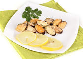Snack of mussels and lemon on plate isolated on white — Stock Photo