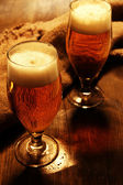 Glasses of beer on wooden table close-up — Stock Photo