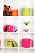 Scatole di vimini di colore sugli scaffali armadi — Foto Stock