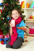 Kleines mädchen mit rosa schal und glas milch in der nähe weihnachtsbaum — Stockfoto
