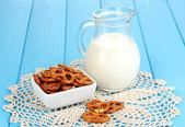 Saborosos pretzels na jarra tigela e leite branca close-up de madeira mesa — Foto Stock