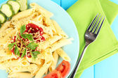 Rigatoni pasta dish with tomato sauce on blue wooden table close up — Stock Photo