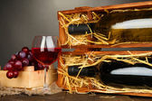 Dřevěné pouzdro s lahví vína, sklenice na víno a hroznovou na šedém pozadí — Stock fotografie