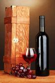 Dřevěné pouzdro s láhví vína na dřevěný stůl na hnědé pozadí — Stock fotografie