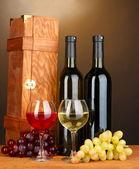 Dřevěné pouzdro s lahví vína na dřevěný stůl na hnědé pozadí — Stock fotografie