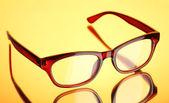 Beautiful glasses on yellow background — Stock Photo