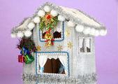 Zdobené vánoční dům na lila pozadí — Stock fotografie