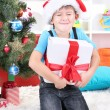 Little boy in Santa hat sits near Christmas tree with gift in hands — Stock Photo