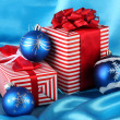 Colorful red gifts with blue Christmas balls on blue background — Stock Photo