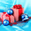 Colorful red gifts with blue Christmas balls, snowflakes and beads on blue background — Stock Photo