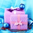 Beautiful purple in peas gifts with blue Christmas balls, snowflakes and beads on blue background — Stock Photo