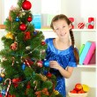 Little girl decorating christmas tree — Stockfoto #18307567