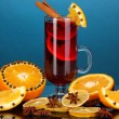 Fragrant mulled wine in glass with spices and oranges around on blue background — Photo