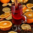 Fragrant mulled wine in glass with spices and oranges around on wooden table — Photo